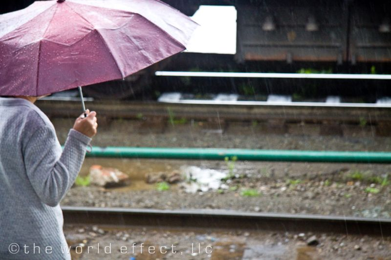 Woman on a platform wating for her train in the rain